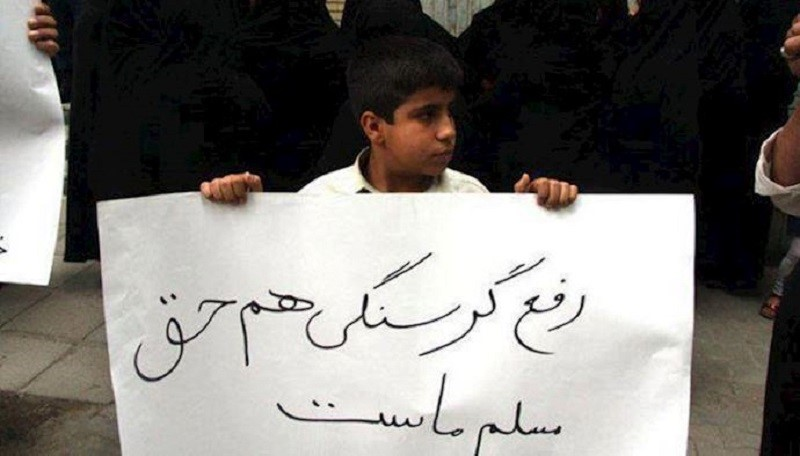 """A little boy in Iran holding a placard with the slogan: """"End to hungry is our inalienable right"""", which is showing the extreme bad economic situation of the people, and the regime as the main cause."""