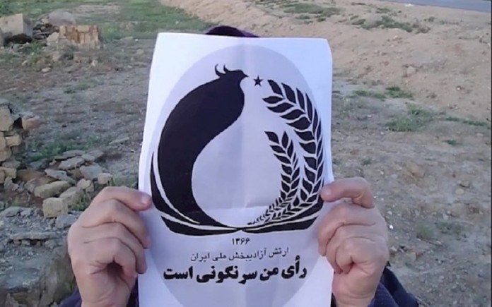 An Iranian holding a paper with the script, 'my vote is the overthrow'