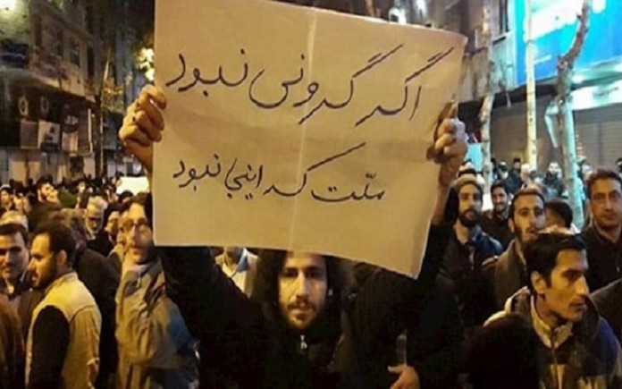 """A picture of a protest by the Iranian people. The man holds a banner that says, """"If things were not so expensive, the people wouldn't be here."""""""