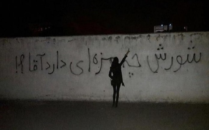 A rebellious young Iranian woman confronting the regime. Slogan written on the wall: 'What a taste a rebellion has, sir.'