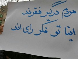 "An Iranian holding a placard with the slogan: ""The people are involved with poverty, and they (the regime) are thinking about votes."
