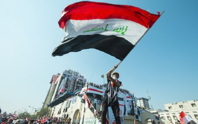 An Iraqi protester holds a flag during the October Revolution, 2019